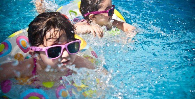 children-wearing-pink-sunglassess-swimming-splashing-on-lilo-rings-wearing-glasses