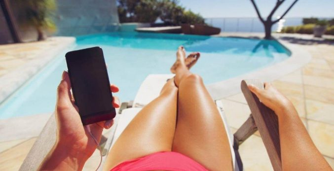 Woman-tanning-next-to a-crystal-clear-swimming-pool-holding-a-cellphone-wearing-a-red-bikini